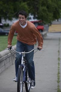 自転車で道路を走る男性の写真素材 [FYI03952818]