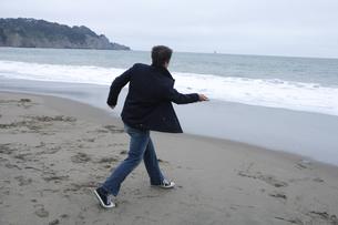 海に石を投げる男性の写真素材 [FYI03952831]