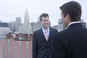 ビルの屋上で会話するビジネスマンの写真素材 [FYI03952837]