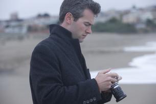 浜辺でカメラを持った男性の写真素材 [FYI03952838]