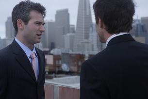 ビルの屋上で会話するビジネスマンの写真素材 [FYI03952839]