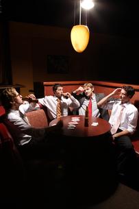 バーのテーブルでビールを飲む男性4人の写真素材 [FYI03952864]