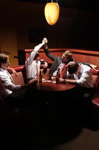 バーのテーブルでビールを飲む男性4人の写真素材 [FYI03952865]