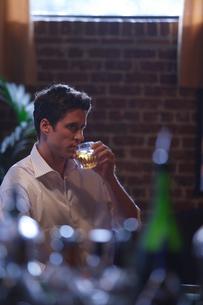 バーカウンターでお酒を飲む男性の写真素材 [FYI03952875]