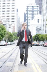 歩きながら携帯電話で話すビジネスマンの写真素材 [FYI03952882]