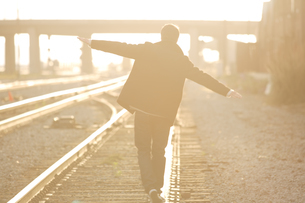 線路の上を歩く男性の後姿の写真素材 [FYI03952929]