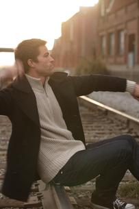 線路の上に座る男性の写真素材 [FYI03952935]