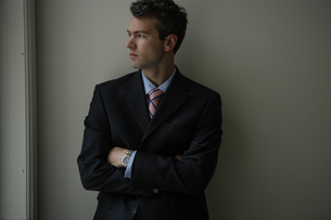 オフィスの壁際に立つビジネスマンの写真素材 [FYI03952944]