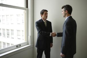 会社の窓際で握手するビジネスマンの写真素材 [FYI03952950]