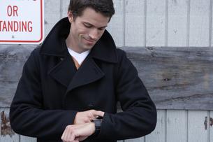 倉庫の前に立って時計を見る男性の写真素材 [FYI03952963]