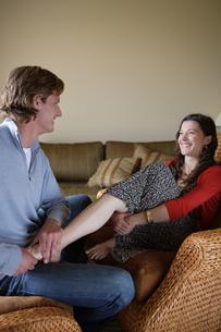 ソファで女性の脚をマッサージする男性の写真素材 [FYI03952999]