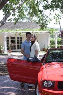 車のそばで寄り添うカップルの写真素材 [FYI03953051]