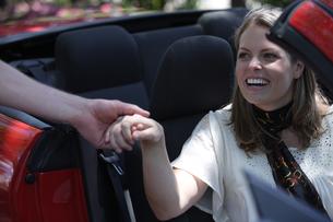 助手席の女性に手を差し伸べる男性の写真素材 [FYI03953052]