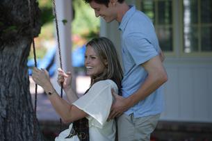 庭のブランコに乗る女性を押す男性の写真素材 [FYI03953055]