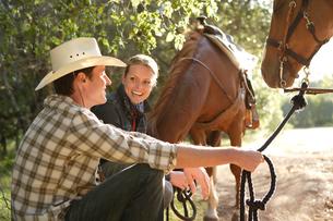 乗馬中に休憩をとるカップルの写真素材 [FYI03953111]