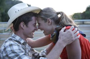 カウボーイハットをかぶり顔を寄せ合うカップルの写真素材 [FYI03953117]