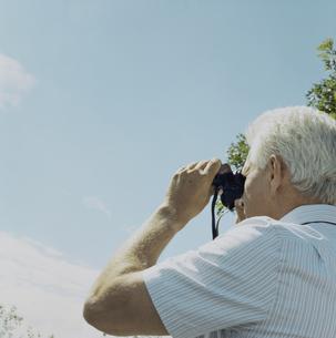 双眼鏡で景色を眺める男性の写真素材 [FYI03953130]