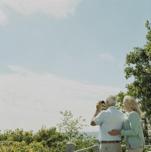 双眼鏡で景色を眺める男性と寄り添う女性の写真素材 [FYI03953131]