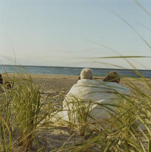 ブランケットを羽織って海岸に座る夫婦の写真素材 [FYI03953142]