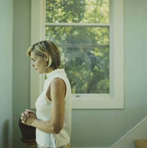 窓際で祈りを捧げる女性の写真素材 [FYI03953174]