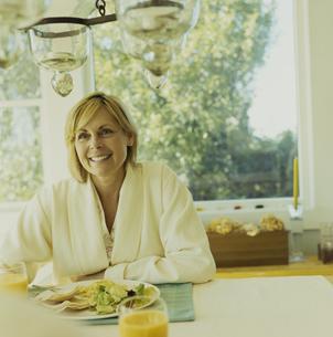 ガウンを着て朝食を食べる女性の写真素材 [FYI03953175]