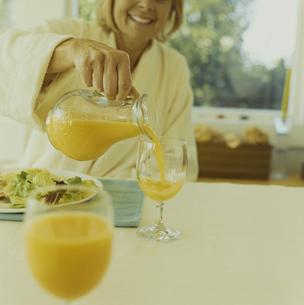 ガウンを着て朝食のオレンジジュースを注ぐ女性の写真素材 [FYI03953177]