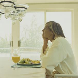 ガウンを着て朝食を食べる女性の写真素材 [FYI03953180]