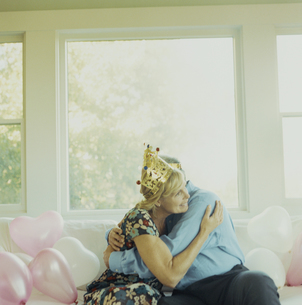王冠をかぶってソファーの上で抱擁する夫婦の写真素材 [FYI03953183]
