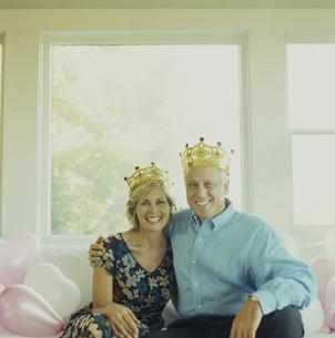 王冠をかぶってソファーの上で寄り添う夫婦の写真素材 [FYI03953184]