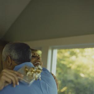 プレゼントを受け取り夫に抱擁する妻の写真素材 [FYI03953189]