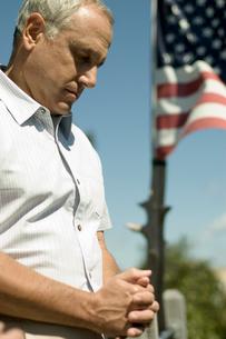 アメリカ国旗の前で祈りを捧げる男性の写真素材 [FYI03953191]