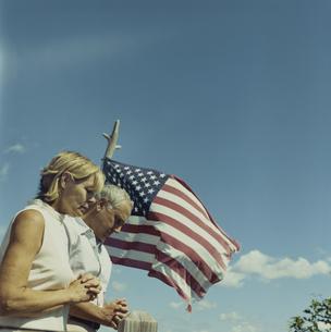 アメリカ国旗の前で祈りを捧げる夫婦の写真素材 [FYI03953197]