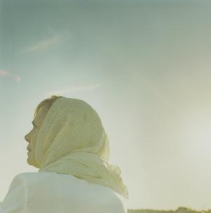 スカーフを巻いて夕陽を眺める女性の写真素材 [FYI03953204]