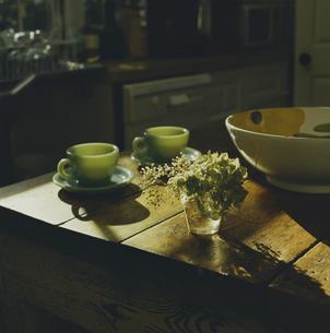 キッチンテーブルに置かれたコーヒーカップと花の写真素材 [FYI03953214]