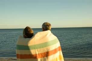 夕陽の海外で毛布に包まる夫婦の写真素材 [FYI03953222]