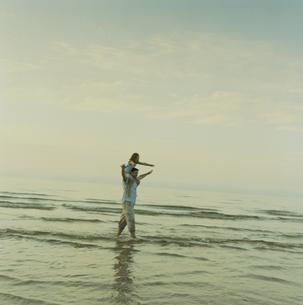 海岸で娘を肩車して散歩する父の写真素材 [FYI03953238]