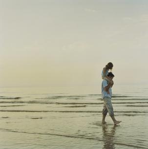 海岸で娘を肩車して散歩する父の写真素材 [FYI03953240]