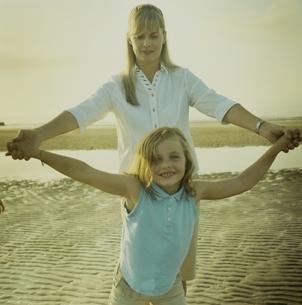 海岸で手を繋ぎあって遊ぶ母と娘の写真素材 [FYI03953242]