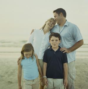 海岸で寄り添う夫婦と息子と娘の写真素材 [FYI03953246]
