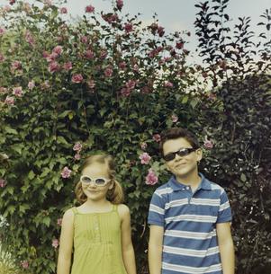 花の前でサングラスをかけて微笑む少年と少女の写真素材 [FYI03953262]