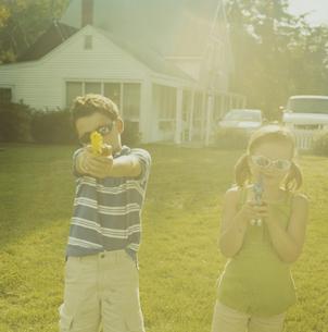 サングラス7をかけて水鉄砲で遊ぶ少年と少女の写真素材 [FYI03953264]