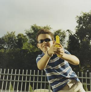 サングラス7をかけて水鉄砲で遊ぶ少年の写真素材 [FYI03953266]
