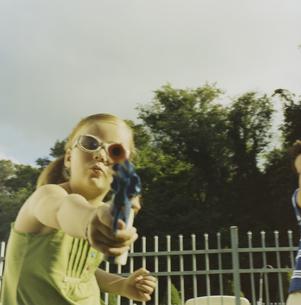 サングラス7をかけて水鉄砲で遊ぶ少女の写真素材 [FYI03953270]