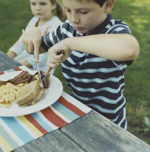 バックヤードでベーコンエッグを食べる少年の写真素材 [FYI03953272]