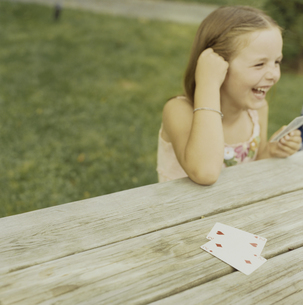 テーブルの上でトランプをして遊ぶ少女の写真素材 [FYI03953275]