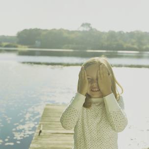 湖のデッキで手で顔を隠して笑う少女の写真素材 [FYI03953287]