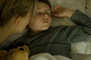 ぬいぐるみを抱っこして眠る少年と母親の写真素材 [FYI03953289]