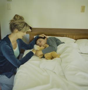 ぬいぐるみを抱いて寝る少年と寄り添う母の写真素材 [FYI03953297]