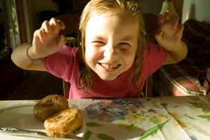 朝食のベーグルを食べる少女の写真素材 [FYI03953319]