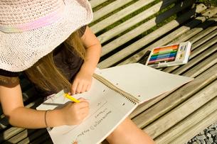 スケッチブックにお絵かきをする少女の写真素材 [FYI03953329]